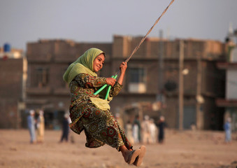 A girl plays on a home made merry-go-round in a vacant lot in Peshawar