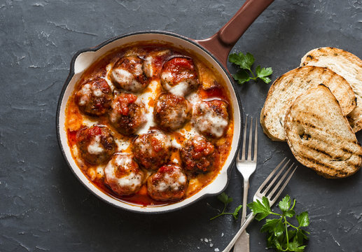 Baked meatballs with mozzarella and tomato sauce in a cast iron skillet on a dark background, top view