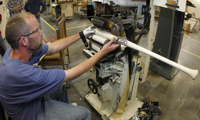 Hillerich & Bradsby employee Newton foil stamps the Louisville Slugger and World Series logos on bats for Detroit Tigers catcher Avila in Louisville
