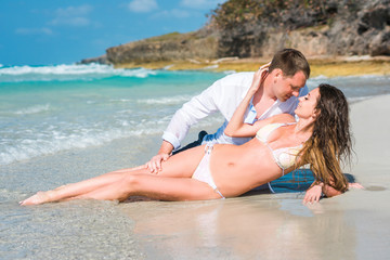 Beautiful young woman with long blond curly hair in white swimsuit and man lie on the sand of caribbean coastline near rocks