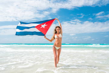 Beautiful young blond woman in white bikini is holding the cuban flag in her arms on beach of caribbean sea