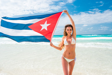 Beautiful young blond woman in white bikini holds the cuban flag in her arms on beach of caribbean sea