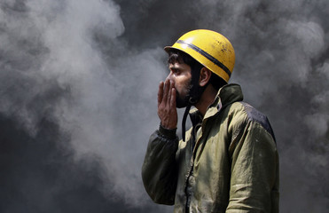 A Kashmiri firefighter covers his nose as smoke billows from a store in a silk factory complex during a fire in Srinagar