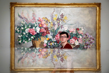 """A visitor walks past the painting """"Various Flowers"""" by Konchalovsky at the Museum of Russian Impressionism in Moscow"""