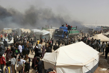 Jordanian firefighters and Syrian refugees extinguish a fire at Al Zaatari