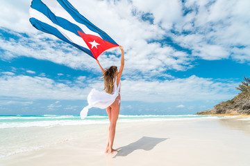 Beautiful young blond woman in white dress and bikini swimsuit is standing a back holding the cuban flag in her arms on beach of caribbean sea