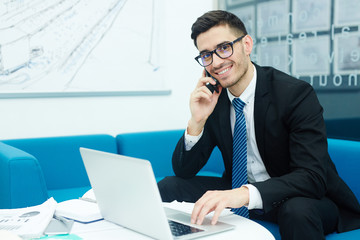 Modern agent with cellphone calling at workplace