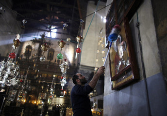 A worker cleans a picture at the Church of the Nativity ahead of  U.S. President Obama's visit, in Bethlehem