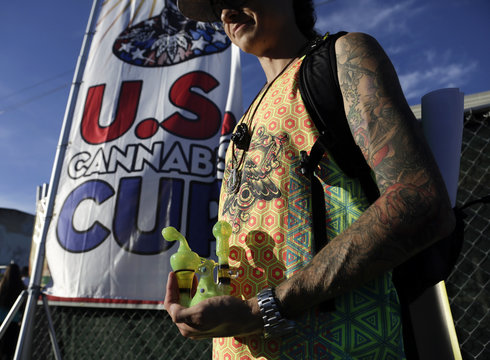 An attendee holds a water pipe at the High Times U.S. Cannabis Cup in Seattle, Washington