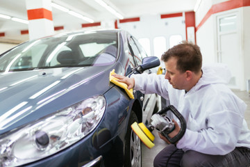 A man cleaning car with microfiber cloth and holding orbital polisher. Car detailing (or valeting) concept. Front lights protected with isolation blue tape. Selective focus.