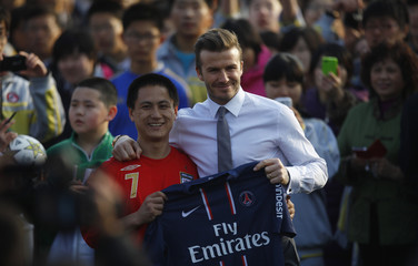 Former England captain Beckham poses for pictures with student after soccer game with students at middle school during his visit in Beijing