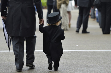 A young racegoer stands between other spectators on the fifth day of the Royal Ascot horse racing festival