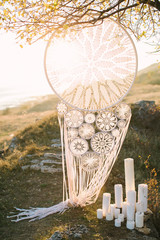 big white Dreamcatcher connected by a hook hanging on a tree in beams of the sunset sun, white candles of the different sizes. knitting, handmade, wedding, decor - concept.