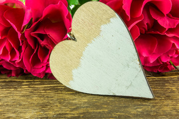 Red roses with a white heart on a rustic wooden table