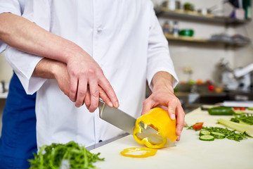 Trainee and chef slicing ingredients for salad
