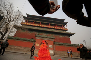Passers-by take pictures of Chinese artist Kong Ning in her costume made of hundreds of orange plastic blowing horns during her art performance raising awareness of the hazardous smog in front of the Drum tower in a historical part of Beijing