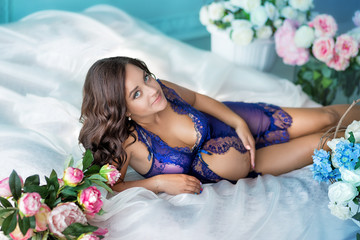 Beautifull young brunette pregnant woman in awesome sexy purple dress close to blue sofa and cute flowers.