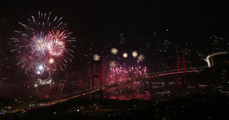 The Bosphorus Bridge that links the city's European and Asian sides, with the European side in the background, lights up with a fireworks display during the Republic Day celebrations in Istanbul