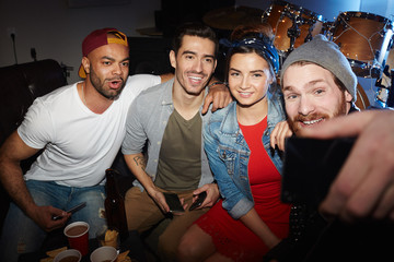 Group of modern trendy people chilling at night club party, posing for selfie photo and having fun