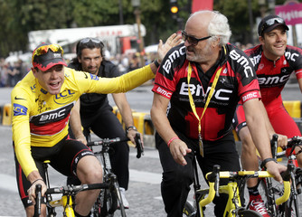 Evans of Australia celebrates on the Champs Elysees next to Rihs after he won the 98th Tour de France cycling race in Paris