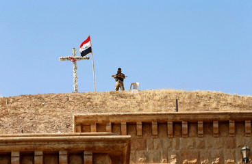An Iraqi Christian soldier guards the church of Saint Barbara after it was recaptured from Islamic State in Qaraqosh