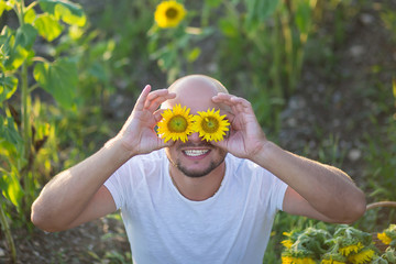 Portrait of young happy man smiling and sitting on a sun flower field