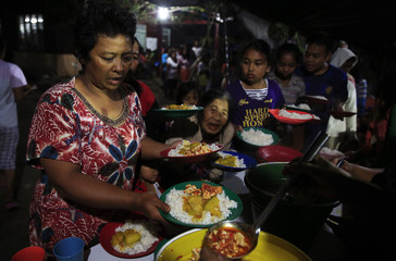 A villager holds plates as she queues for dinner after being evacuated from her home due to the eruption of Mount Sinabung, at a temporary shelter in Kabanjahe