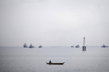 Man sits in an unpowered boat as ships in the background lie at anchor in the Singapore Strait
