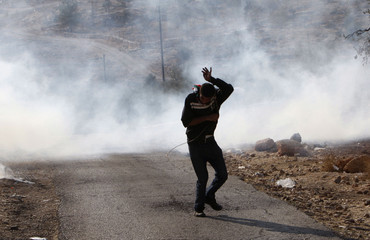 Palestinian protester runs away from tear gas fired by Israeli soldiers during a protest in Bilin