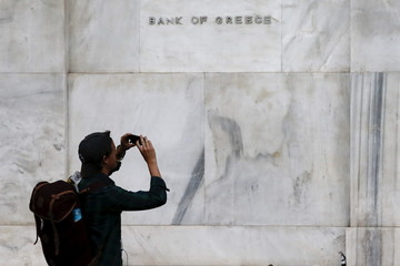 A man takes pictures with his mobile phone next to the Bank of Greece building in Athens