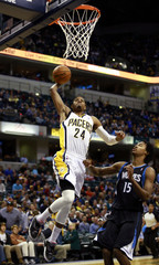 Indiana Pacers forward George dunks the basketball on Minnesota Timberwolves forward Gelabale during their NBA basketball game in Indianapolis