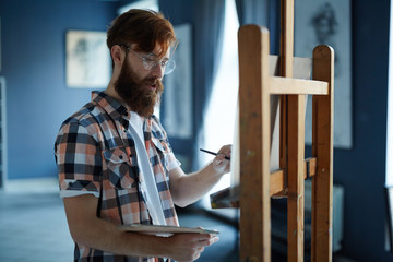 Portrait of focused contemporary artist, red-haired man with beard wearing glasses, painting picture on canvas in art studio