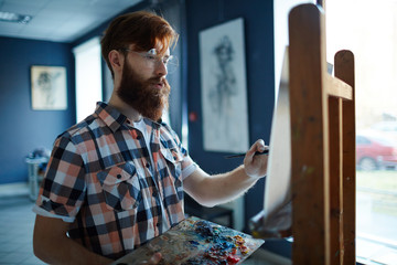Portrait of focused contemporary artist, red-haired bearded man, painting picture on canvas in art studio