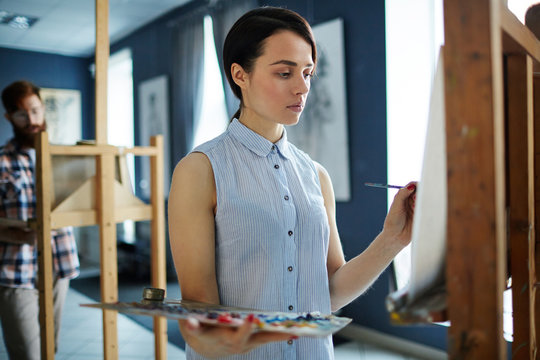 Portrait of young beautiful woman painting picture on easel standing in row of students in art class looking focused and concentrated