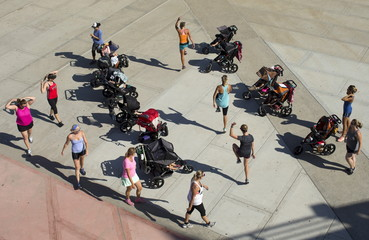 Young children sit watching from strollers as their mothers workout along the beach in Oceanside, California