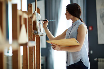 Portrait of talented young woman painting picture on canvas in art studio with inspiration