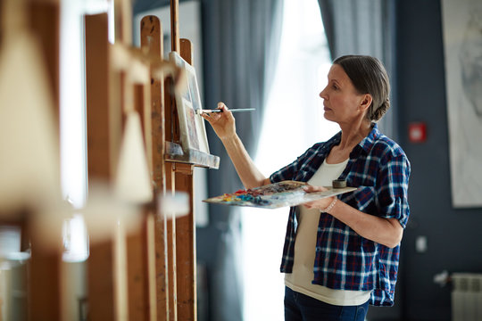 Portrait of elegant mature woman painting oil picture with inspiration in art studio