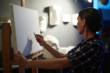 Portrait of talented mature woman drawing plaster head models on blank white canvas in artists studio