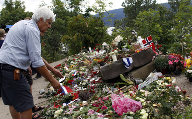 People pay their respect to the victims of the shooting spree and bomb attack in Norway on the shore in front of Utoeya island