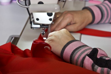 Women's hands sew clothing on a sewing machine