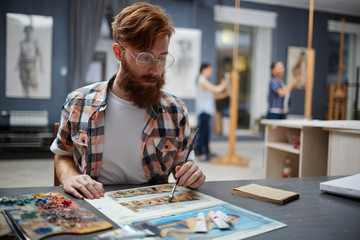 Portrait of contemporary bearded artist working in art studio painting oil pictures looking focused and concentrated