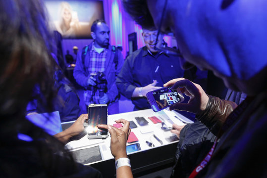 A man uses an Apple iPhone to photograph new Blackberry devices during the RIM Blackberry 10 launch in New York
