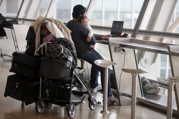 Passenger holds a baby as he uses his laptop in the departure hall at Israel's Ben-Gurion International Airport, during a strike by airline workers