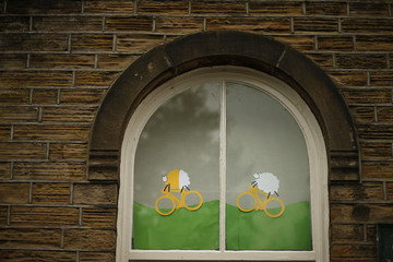 Images of sheep riding yellow bicycles decorate the windows of a church on the route of the Tour de France in Holmfirth