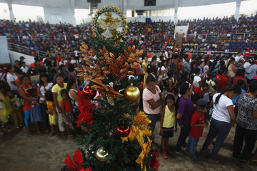 Survivors of onslaught of super Typhoon Haiyan queue in front of Christmas tree during gift giving activity inside astrodome at Tacloban