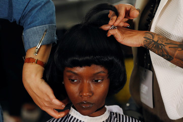 A model has her hair done backstage before a presentation of the Jeremy Scott Spring/Summer 2017 collection during New York Fashion Week in the Manhattan borough of New York