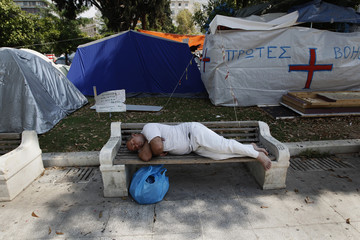 An unidentified man sleeps on a bench in front of tents in Athens