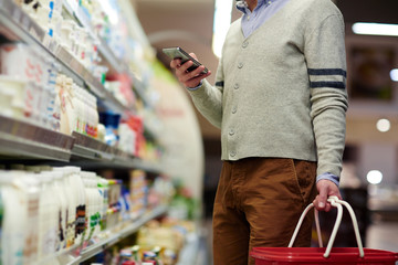 Mid-section portrait of unrecognizable man using smartphone for shopping list, choosing dairy products in supermarket