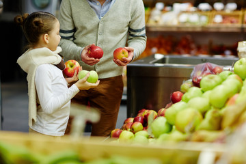 Portrait of cute little girl with dad choosing fresh ripe apples and other fruits in supermarket