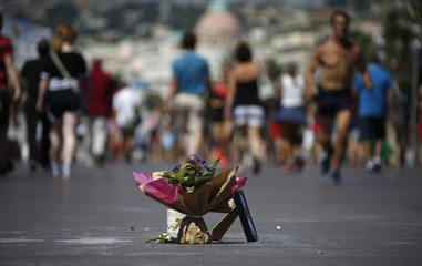People walk near a bouquet of flowers placed in tribute to victims of the truck attack along the Promenade des Anglais on Bastille Day killing scores and injuring as many in Nice